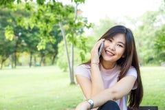 Женщины дела усмехаясь говоря на мобильном телефоне в парке Стоковые Изображения