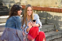 2 женщины деля социальные средства массовой информации с умным телефоном outdoors стоковые фото