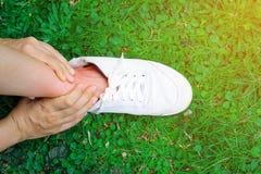 Женщины держат ее sprained лодыжку причиненный аварией Боль пострадавшего чувствуя и использование владения руки на тягостном spr стоковое фото rf