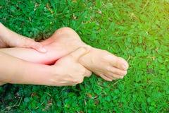 Женщины держат ее sprained лодыжку причиненный аварией Боль пострадавшего чувствуя и использование владения руки на тягостном spr стоковая фотография rf