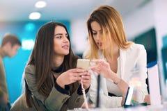 2 женщины держат мобильный телефон в магазине Стоковые Изображения