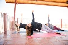 Женщины держа бортовое представление йоги планки Стоковые Фотографии RF