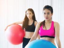 Женщины держа подходящий шарик в классе группы спортзала фитнеса Стоковое Изображение