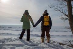 2 женщины держа руки на замороженном береге озера Стоковое Изображение RF
