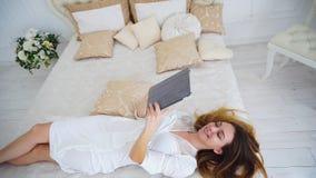 Женщины держа современное устройство и осматривая сегодня новости ` s на интернете лежа на кровати стоковое изображение rf
