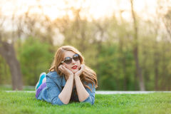 Женщины лежа вниз на зеленой траве Стоковые Фотографии RF