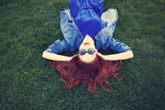 Женщины лежа вниз на зеленой траве Стоковые Изображения