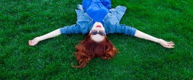 Женщины лежа вниз на зеленой траве Стоковая Фотография