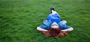 Женщины лежа вниз на зеленой траве Стоковая Фотография RF
