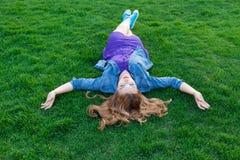 Женщины лежа вниз на зеленой траве Стоковое Фото
