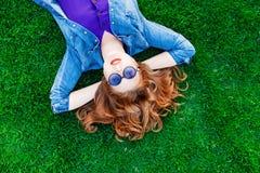 Женщины лежа вниз на зеленой траве Стоковое Изображение RF