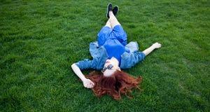 Женщины лежа вниз на зеленой траве Стоковое Изображение