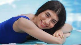 Женщины лежа на ее животе около бассейна видеоматериал