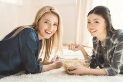 Женщины лежа на ковре и есть попкорн Стоковые Фотографии RF