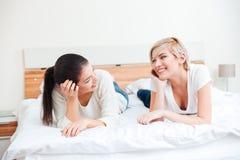 Женщины лежа на кровати и смотря один другого Стоковое фото RF