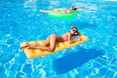 2 женщины лежа на тюфяке воздуха в бассейне Стоковая Фотография RF