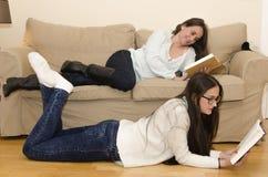 2 женщины лежа на чтении софы Стоковые Фотографии RF
