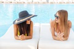 2 женщины лежа на deckchair outdoors на бассейне Стоковые Изображения RF