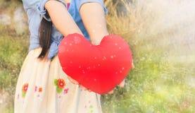 женщины держат большое красное сердце в bokeh яркого блеска светя Стоковые Фотографии RF