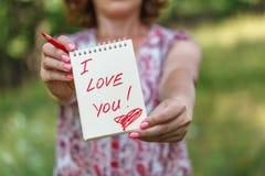 Женщины держат карточку подарка дня валентинки в ее руках с я тебя люблю Стоковая Фотография RF