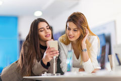 2 женщины держат мобильный телефон в магазине Стоковая Фотография