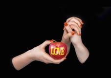 2 женщины держа их руки и показывая яблоко с lov слова Стоковое Изображение