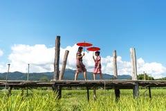 Женщины держа красные зонтик и прогулку на деревянном мосте в зеленом рисе field Mae Hongson Таиланд Стоковая Фотография RF