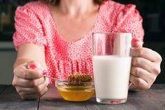 Женщины держа молоко на таблице Стоковые Изображения