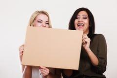 2 женщины держа пустую доску Стоковая Фотография RF