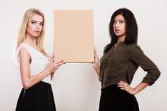 2 женщины держа пустую доску Стоковые Фотографии RF