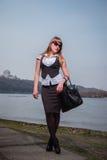 Женщины держа солнечные очки при русые волосы, одетые в белом и черной, портрете, солнечном дне, с рекой и городом на th Стоковая Фотография