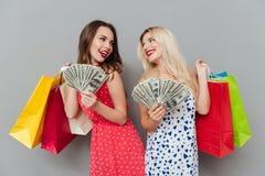 2 женщины держа хозяйственные сумки и деньги Стоковые Изображения
