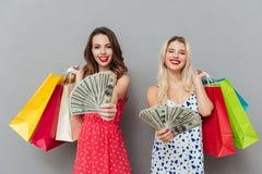 2 женщины держа хозяйственные сумки и показывая деньги Стоковое Изображение