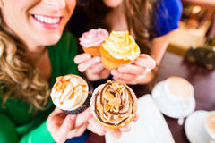 Женщины есть булочки пока выпивать кофе Стоковая Фотография
