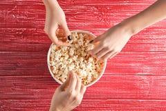 Женщины есть вкусный попкорн на таблице Стоковые Изображения