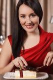 Женщины есть десерт. Красивые женщины в красном платье есть торт a Стоковое Изображение