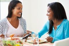 2 женщины есть еду совместно дома Стоковая Фотография