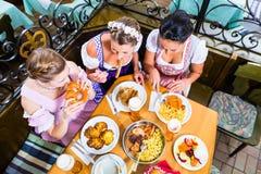 Женщины есть обед в баварском ресторане Стоковая Фотография