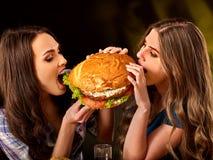Женщины есть фаст-фуд Gils ест гамбургер с ветчиной стоковые фото