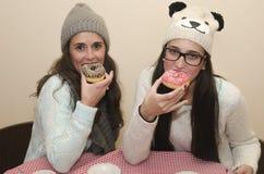 2 женщины есть donuts Стоковое Изображение