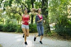 Женщины детенышей подходящие jogging outdoors Стоковое Изображение