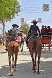 2 женщины ехать в ярмарке Севильи, Андалусии, Испании Стоковые Фото