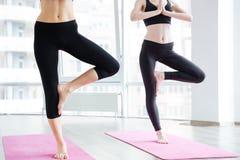 2 женщины делая балансируя представление на розовую циновку йоги Стоковые Фотографии RF