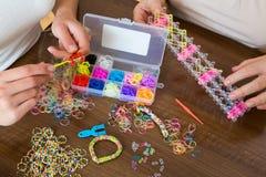 Женщины делая декоративные браслеты с эластичными резиновыми лентами Стоковые Фото