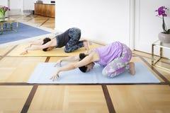 2 женщины делая изменение Balasana йоги дома Стоковые Изображения