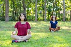 Женщины делая йогу в парке Стоковое Изображение RF