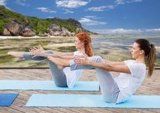 Женщины делая йогу в представлении полу-шлюпки outdoors Стоковое фото RF