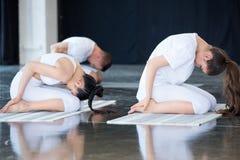 Женщины делая йогу в представлении Balasana ребенка Стоковое Изображение RF