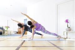 2 женщины делая йогу дома Стоковые Фотографии RF