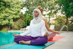 Женщины делая йогу poolside Стоковая Фотография RF